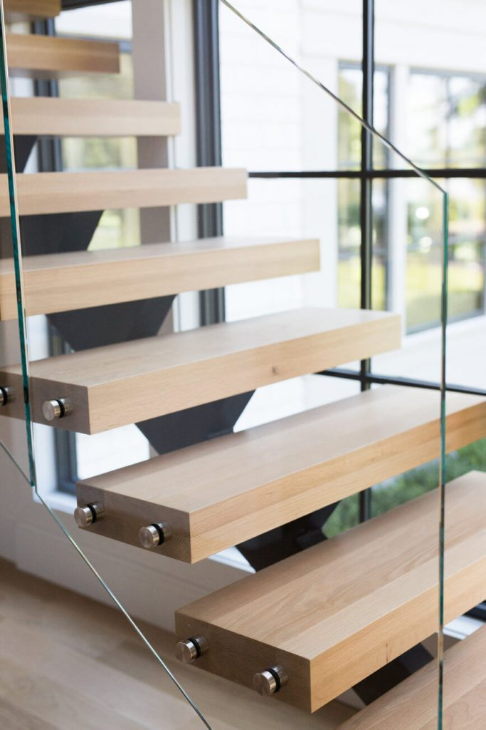 Keuka Studios custom stairs and railing made with white Oak Treads and glass railing.