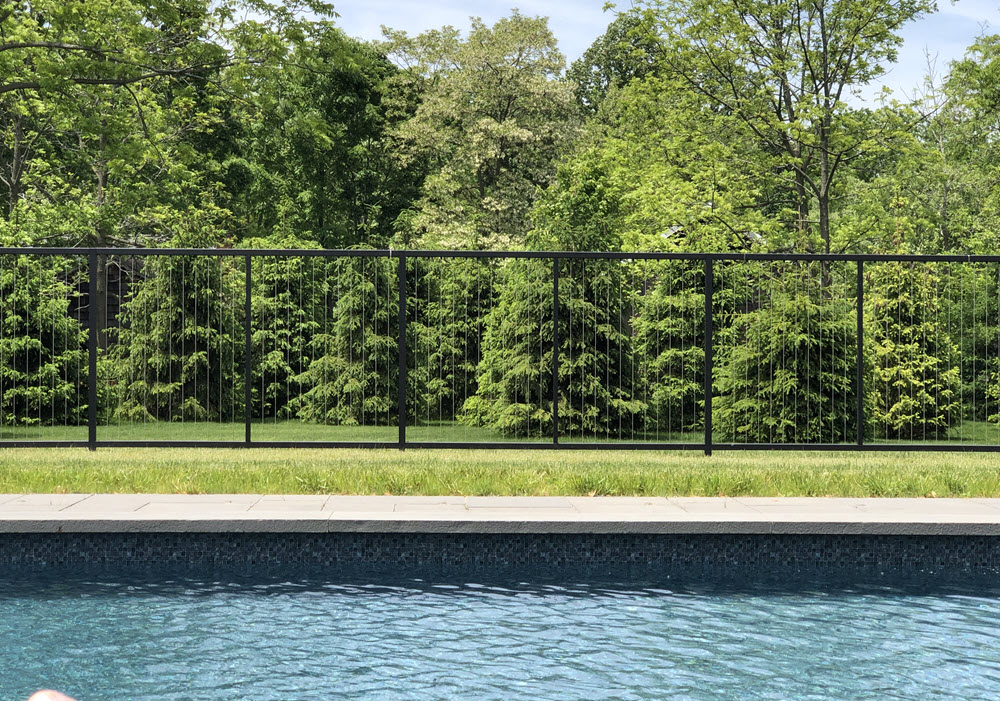 Vertical cable pool fence on lawn