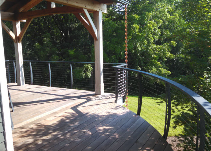 Timber style home with curved deck and cable railing there is rain chain used for water drainage