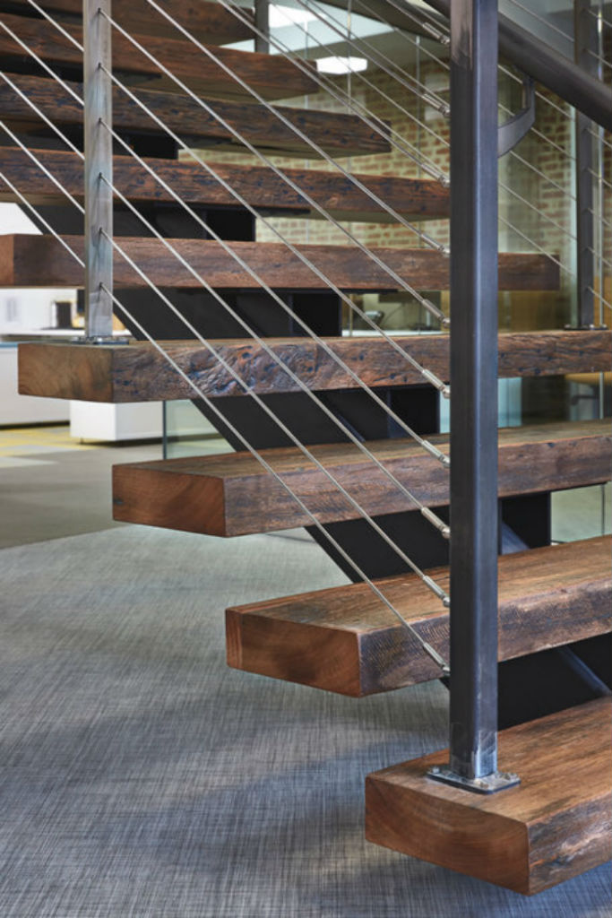Distressed wood treads on rustic industrial staircase.