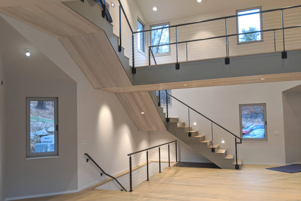 Minimalist railing on modern home with catwalk over looking living room. This narrow bridge allows for large open ceilings.