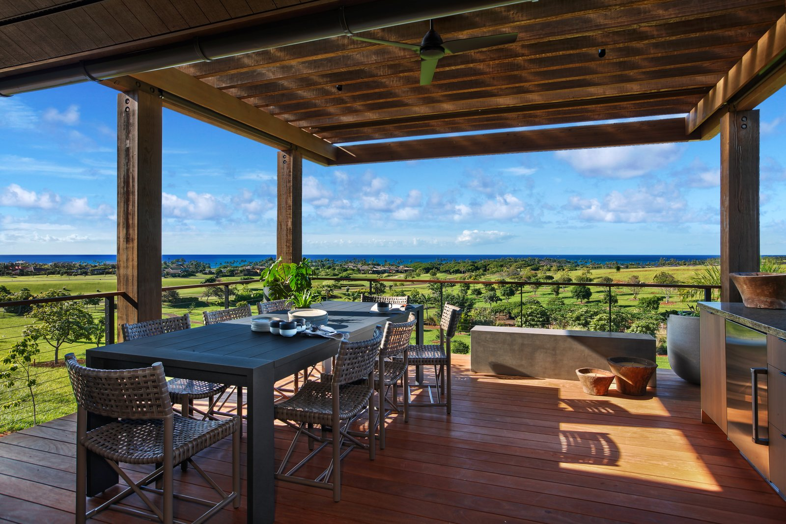 Covered dining deck with cable railing and sweeping ocean views.