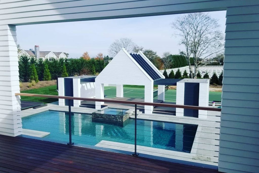 Covered master bedroom deck with stainless steel cable railing system and gray posts overlooking pool area.