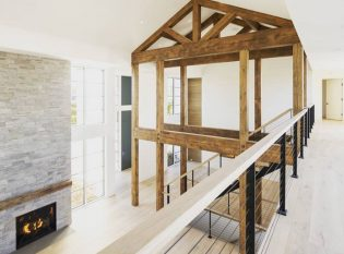 Rustic modern farm house with timber frame and black cable railing system on balcony and stairs