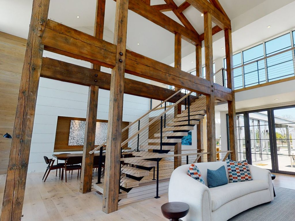 Timber frame structure with floating staircase and cable railings in center of home.