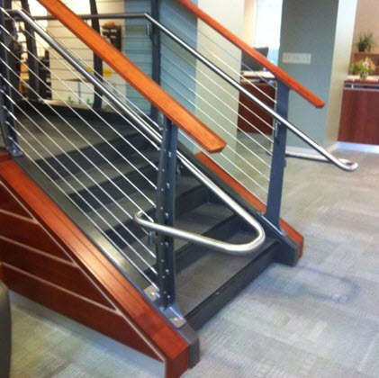 Railing extension on handrail of college lobby staircase