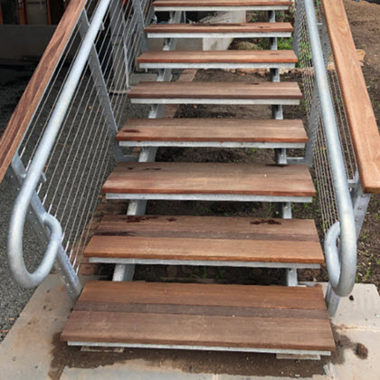Galvanized railing extending beyond the treads.