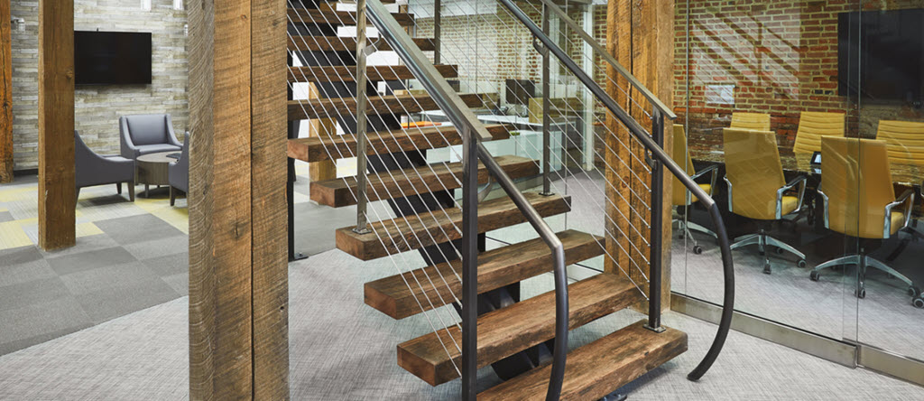 ADA handrail on rustic floating stairs made of steel with wood treads