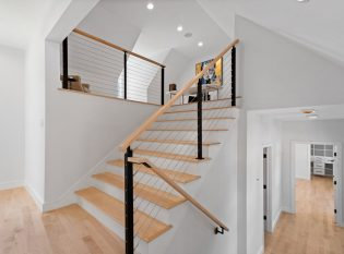 Cable railing system on staircase to loft with handrail