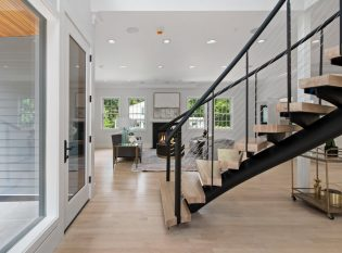 Open living with curved floating staircase in the main entrance