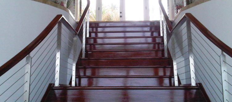 Stainless steel railing posts on mahogany stairs and top rail