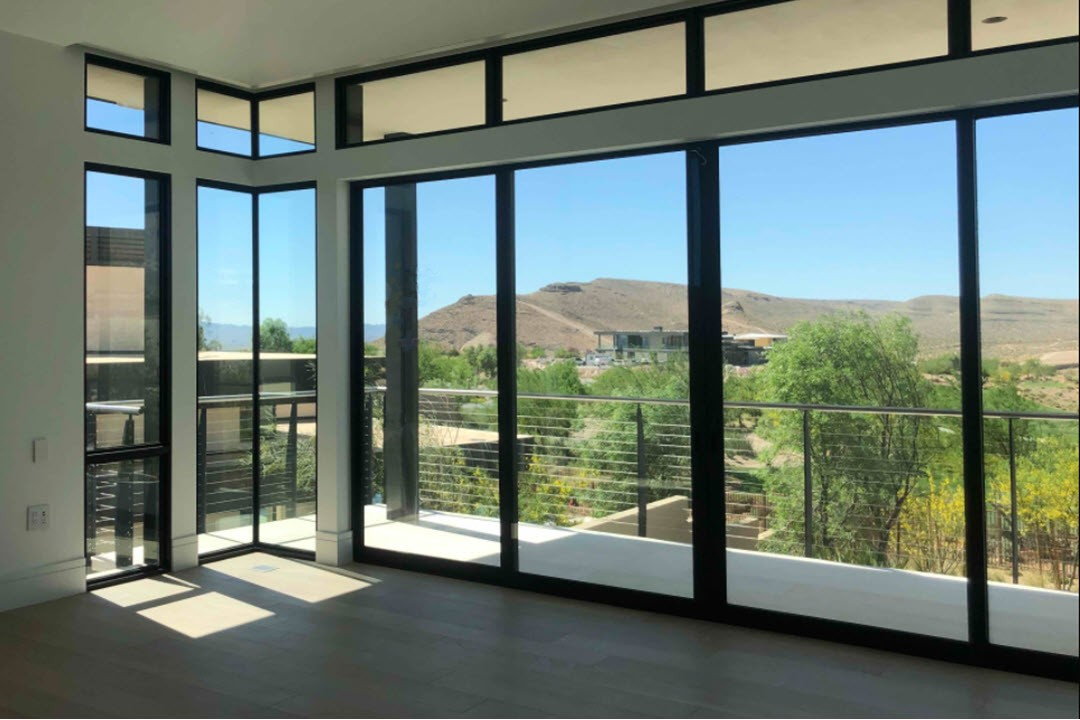 Window wall with mountain view and deck railing