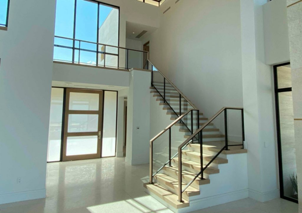 Modern glass stair railing with slim steel frame and wood treads.