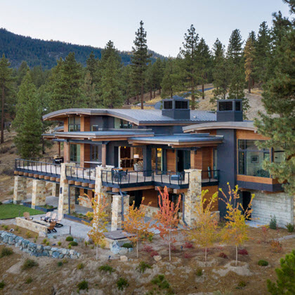 Contemporary Mountain home with curved rooflines and curved cable railings on deck and stone pillars