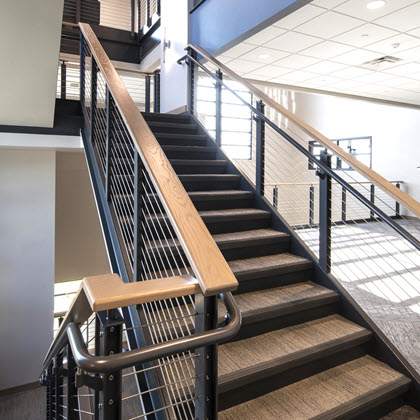Industrial style cable railing system on stairs with ADA handrails