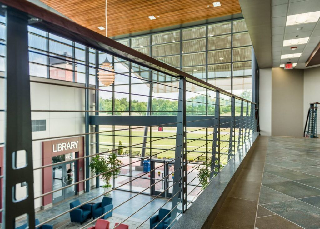 Industrial style railing system with large window view in college atrium.