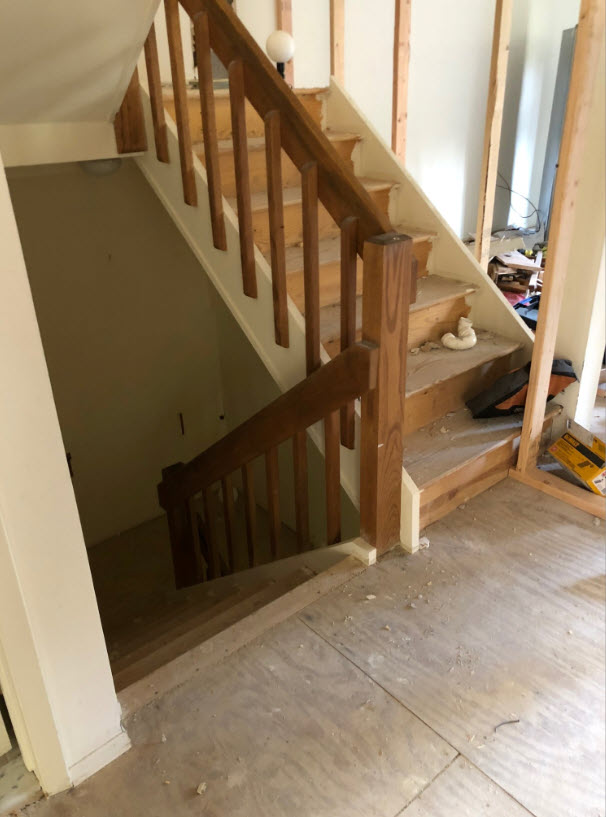 Before of closed stairwell with dated wood spindle stairs