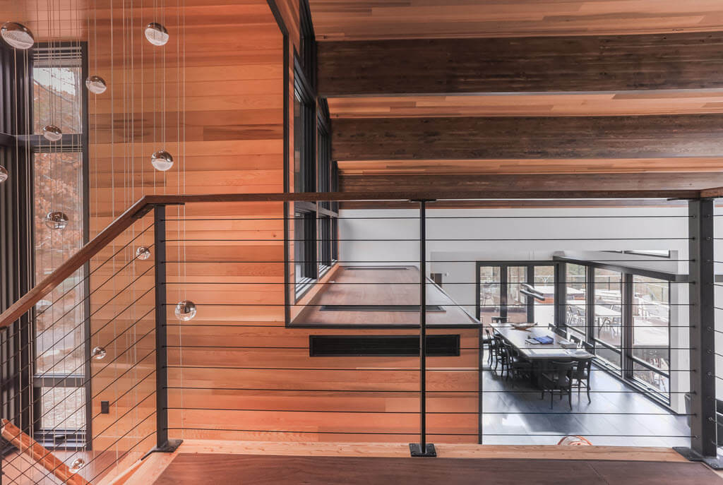 Warm wood throughout the interior of a home with black cable railings on the balcony overlooking the dining room