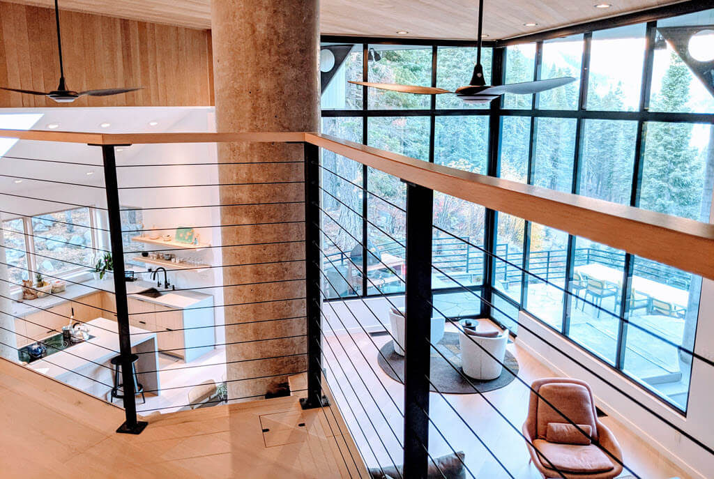 Modern home balcony with black cable railing overlooking great room with floor to ceiling windows