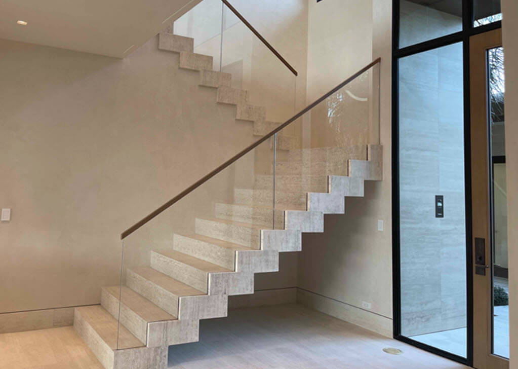Travertine stairs supported by steel structure with glass railing in modern home.