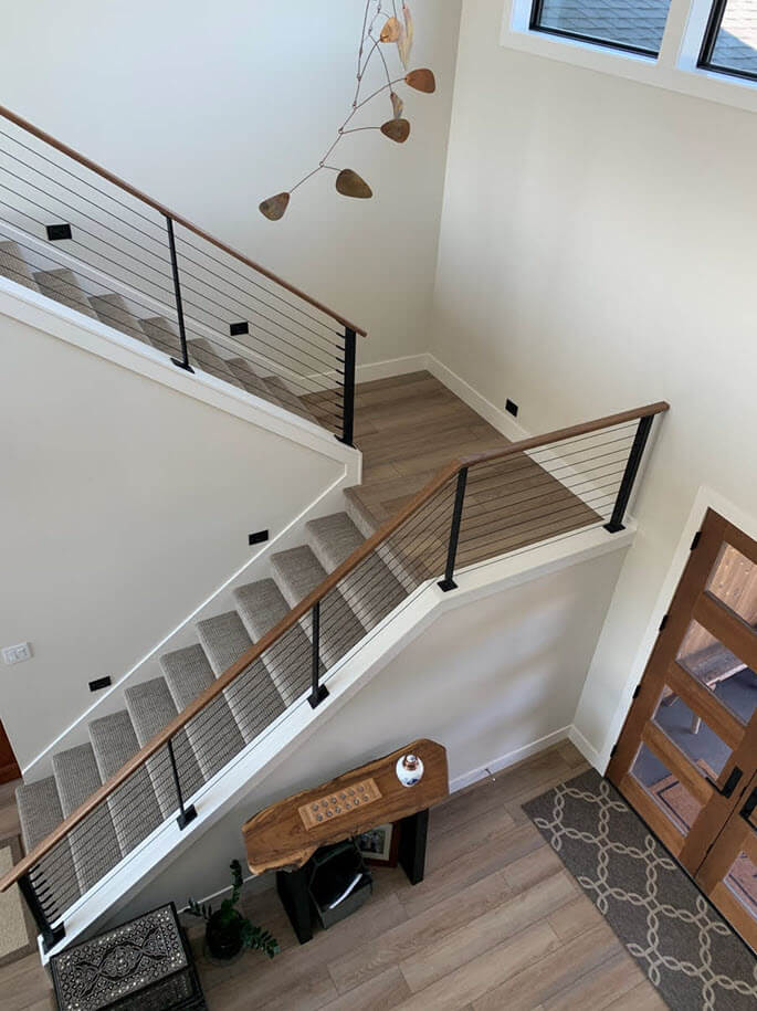Modern staircase with open high ceilings and Ithaca style black railing system.