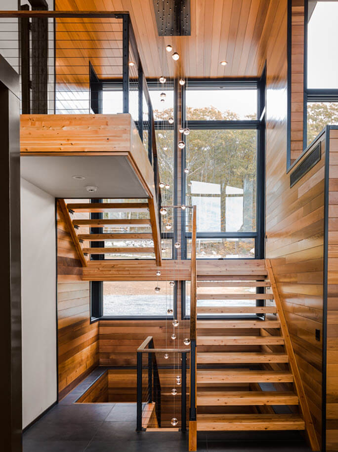 Modern and minimal wood stair with open risers large windows and black railings.