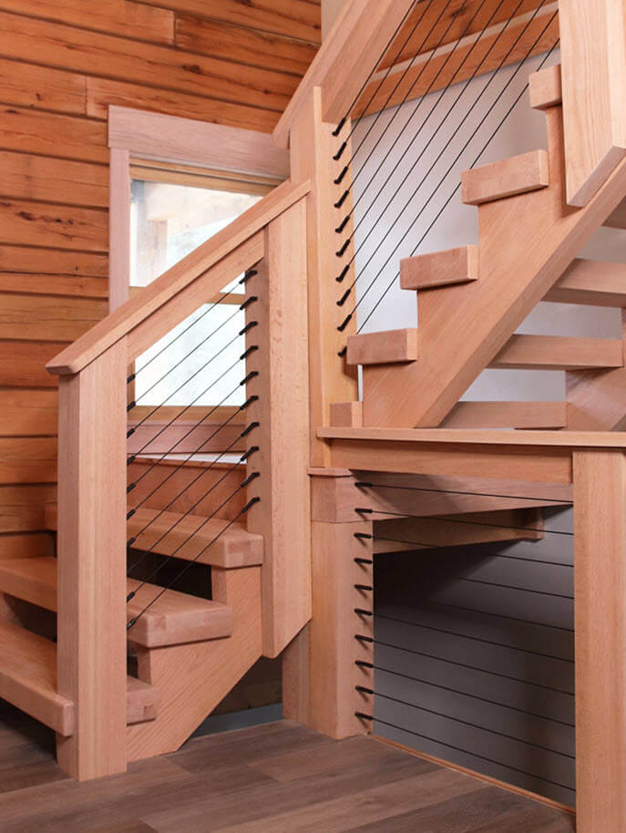 Large timber built rustic log cabin stairs with black cables and fittings.