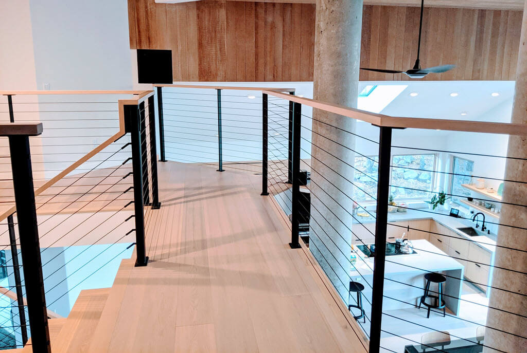 Catwalk with black cable railings overlooking kitchen and expansive mountain views.
